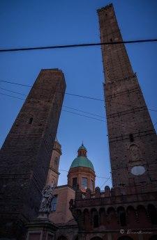 A la izquierda, la torre Garisenda. Esta torre medieval se desvía 3,2 metros respecto de la vertical en su punto más alto, a 48 metros desde el suelo. A la derecha, la torre Asinelli con 97,6 metros de altura y 1,2 metros de inclinación. Durante la Segunda Guerra Mundial fue usada como observatorio para avisar a los servicios de socorro durante los bombardeos.